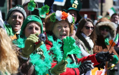 (Boston, MA - 3/18/18) Maria Humphries and Helen Byrne, who came from Ireland for a long weekend, cheer during the St. Patrick's Day Parade in South Boston, Sunday, March 18, 2018. Staff photo by Angela Rowlings.